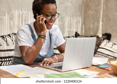 Shot of stylish ethnic female recruiter makes job offer, has telephone conversation, connected to high speed internet, checks information in database on laptop computer, pleased to be promoted.