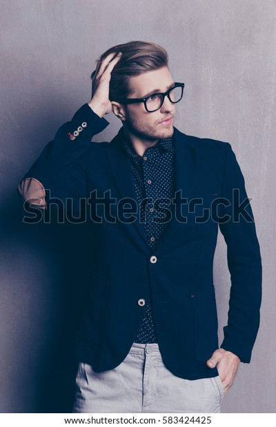 Shot of stylish young man touching his hair and holding hand in a pocket