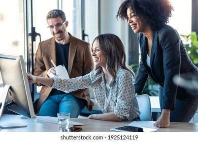 共同作業スペースでの作業のプレゼンテーションのために、コンピュータの周りに立ち並ぶ、成功したビジネスマルチエージチームのショット。