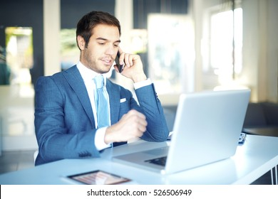 Shot of a successful businessman making call while sitting at desk in front of laptop.