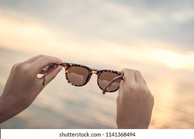 A shot of sunglasses held in hands over the beautiful sunset backround