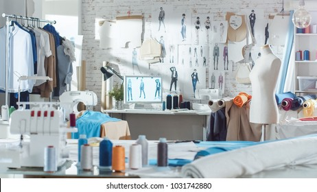 Shot of a Sunny Fashion Design Studio. We See Working Personal Computer, Hanging Clothes, Sewing Machine and Various Sewing Related Items on the Table, Mannequins Standing, Colorful Fabrics.
