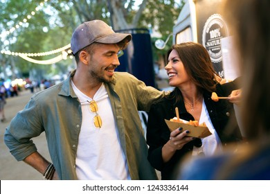 Shot of sweet attractive couple eating potatoes together in eat market in the street.