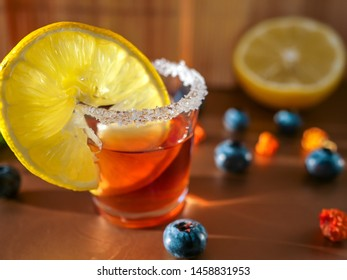 A shot of sweet red alcoholic liquor in a small glass with sugar rim and lemon slice for cold autumn evenings. Blueberry, dried red pepper (capsicum) and lemon half on the background.