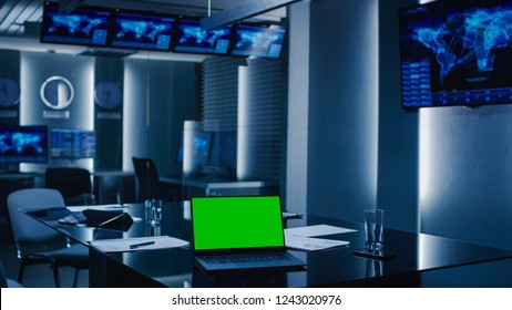Shot of the System Control Monitoring Room. Empty Government Emergency Operations Center. On the Table Laptop Showing Green Mock-up Screen.