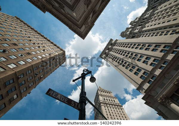 A shot taken from a street corner, pointing high to sky, showing the top of the tall skyscrapers of New York City. A sensation of vertigo.