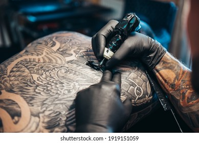 Shot of a tattoo artist hands and a mans back totally tattooed with black ink
