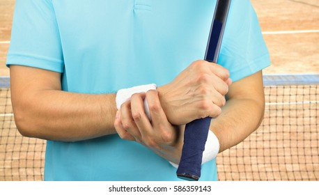 shot of a tennis player with a carpal tunnel syndrome injury in the wrist on a clay court