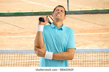 Shot of a tennis player with a elbow injury on a clay court