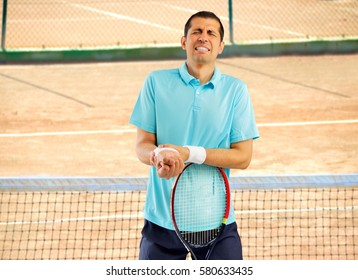 shot of a tennis player with a wrist injury on a clay court