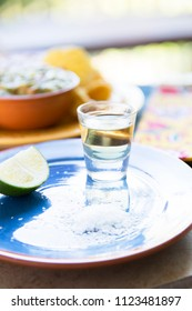 Shot of tequila on blue plate with lime and salt, chips and guacamole out of focus in the background