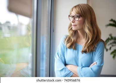 Shot of a thinking middle aged woman looking out the window.