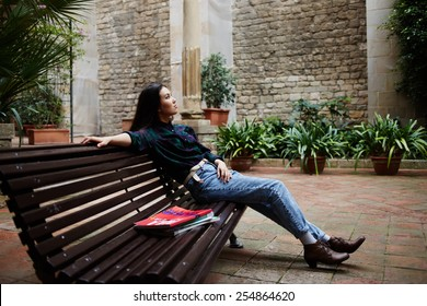 Shot of a thoughtful young female student leaning on a campus bench and resting after classes, beautiful young woman enjoying her leisure time outdoors
