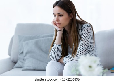 Shot of thoughtful young woman sitting on sofa at home.
