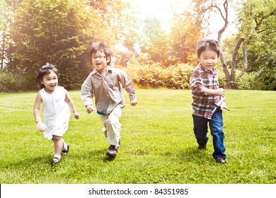 A shot of three Asian kids running in a park (focus in the middle kid)