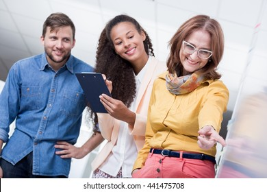 Shot of three casually dressed employees in a modern workplace assesing some designs together
