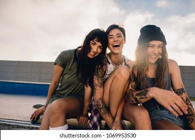 Shot of three smiling girls hanging out at skate park. Group of women friends sitting outdoors at skate park and laughing.