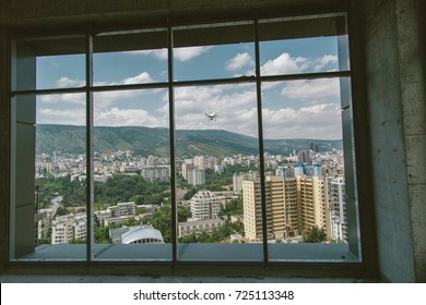 Shot throw the window white drone with camera flying near house, cityscape, estate, sky and mountains on background