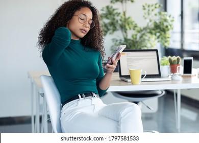 会社で携帯電話を持つ首の痛みを持つ疲れた若い女性の写真。