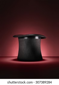 Shot of a traditional magicians style top hat set up for a trick or illusion on a red background with space left for the designer to add an object or type.