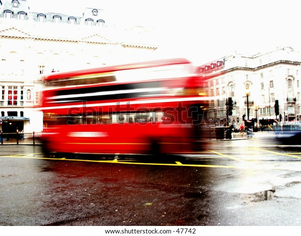 A shot of a traditional red London bus in motion. The background is purposely over-exposed to gain the bus movement and also to make the bus 'pop'