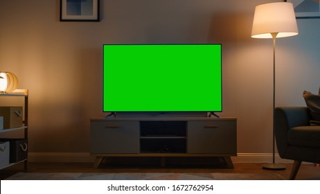 Shot of a TV with Horizontal Green Screen Mock Up. Cozy Evening Living Room with a Chair and Lamps Turned On at Home.
