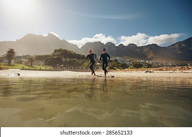 Shot of two athletes running into the water, practicing for triathlon competition. Young man and woman in wet suits preparing for the race at the lake.
