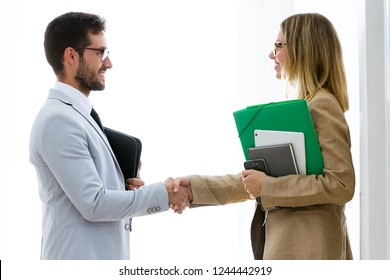 Shot of two attractive bussines partners shaking their hands in the office.
