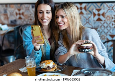 Shot of two beautiful young women friends eating burgers while looking smart phone in the restaurant.