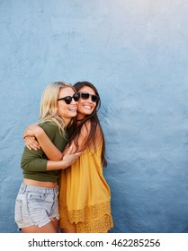 Shot of two best friends embracing over blue wall. Young women having great time together.