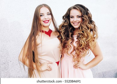Shot of two best friends embracing over gray wall . Young women having great time together. Sisters at the prom with gorgeous long curly hair . Professional make-up and hairstyle .