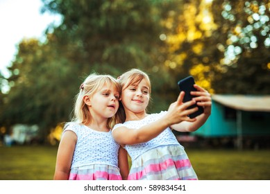 Shot of two blonde sisters posing for a picture on the mobile phone outdoors.