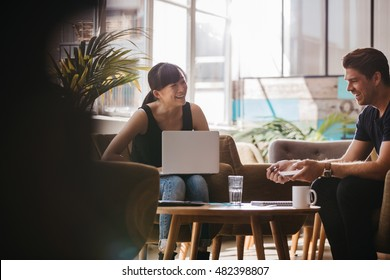 Shot of two business partners sitting in office lobby and smiling. Woman with laptop discussing business ideas with male colleague.
