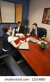 A shot of two businesswomen and a businessman playing cards at business meeting.