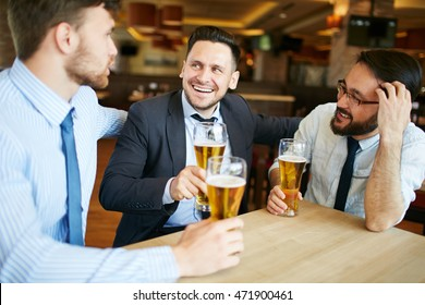 Shot of two Caucasian and one Asian business partners in formal attire laughing and enjoying beer in bar after work