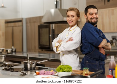 Shot of two cheerful professional kitchen chefs posing back to back together at the restaurant kitchen. Happy handsome chef and his female trainee smiling to the camera proudly.