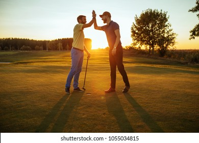 Shot of two golfers congratulating each other with a high five