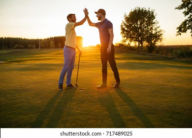 Shot of two golfers giving high five on the golf course.