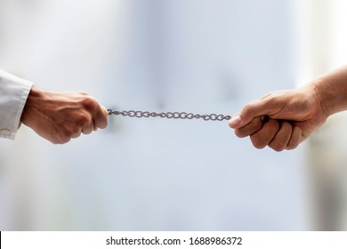 Shot of two hands on the end of a rusted metal chain pulling from both sides with blurred background and selective focus. Male hand playing tug of the war with a metal chain.