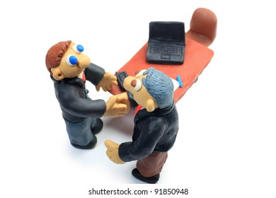 Shot of two plasticine businessmen shaking their hands in office. Isolated over white background.