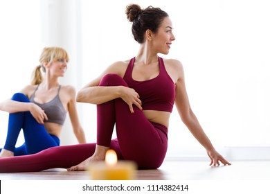 Shot of two pretty young women practicing yoga at home. Marichyasana pose.