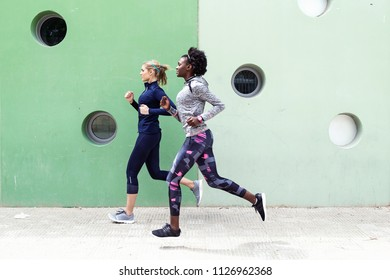 Shot of two sporty young women running together in the city.