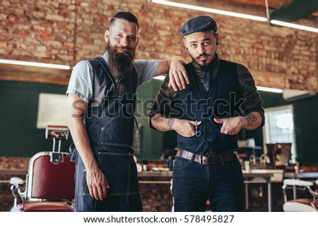 Shot of two stylish man posing together at salon. Barber with client standing at barbershop.