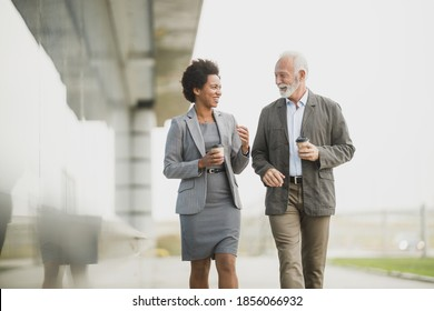 Shot of two successful multi-ethnic business people having fun while walking during a coffee break in front of the office building.