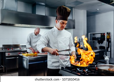 Shot of two young chefs in the kitchen preparing food