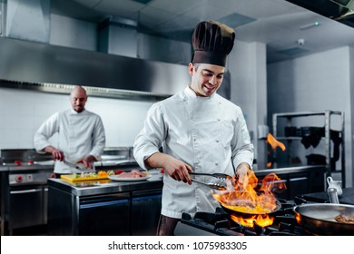 Shot of two young cooks preparing food in the kitchen
