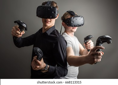Shot of two young man standing with VR goggles and keep joysticks or finger as a gun