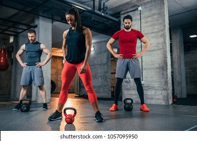 Shot of two young men and a woman with kettle bells at the gym