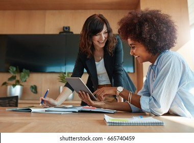 Shot of two young woman working together on digital tablet. Creative female executives meeting in a office using tablet pc and smiling.