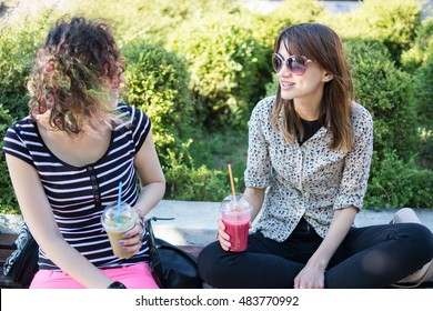 Shot of two young women in casual clothing wearing sunglasses talking and laughing on a sunny afternoon in nature. Sitting on bench in a city park and holding cups with fresh fruit smoothies